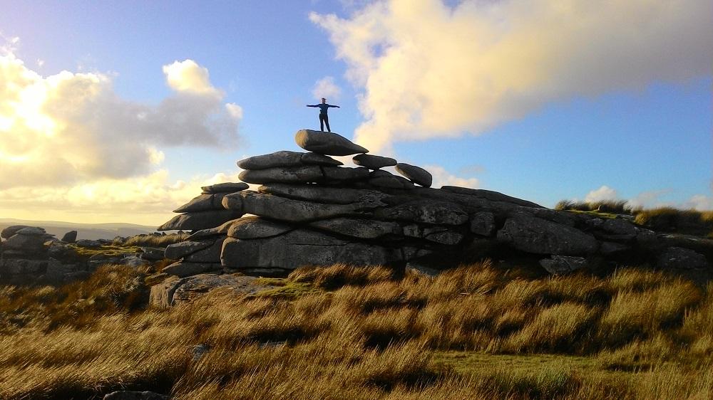 žena stojící rozpažená na obrovské hordě velkých kamenů