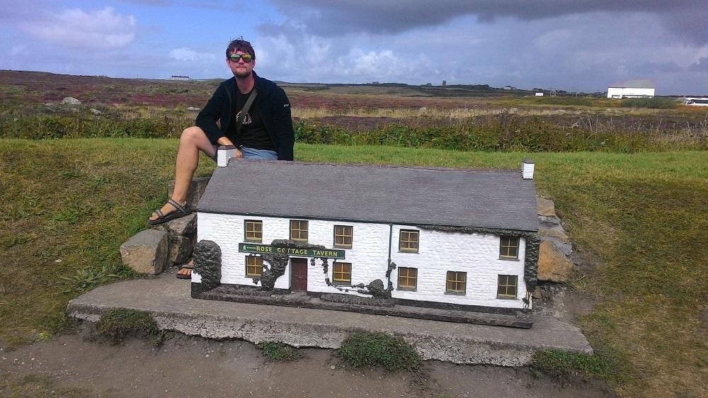 Muž sedící u miniatury domu