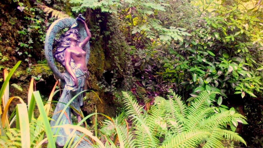 socha víly zasazená v divokém kapradí
