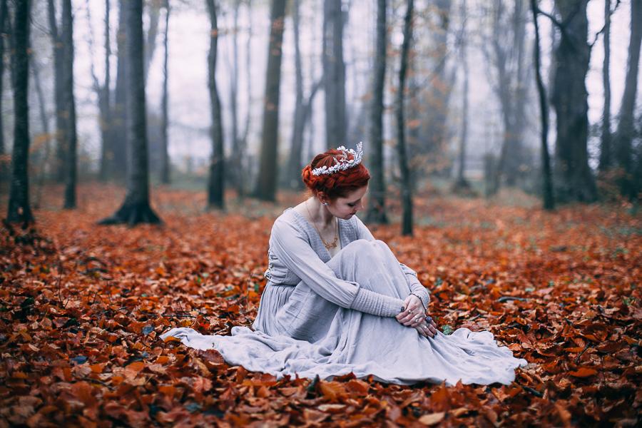 Krásná bohyně sedící na spadaném listí v lese